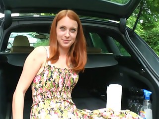 Yummy ginger girlfriend is masturbating her whorish pussy in the trunk